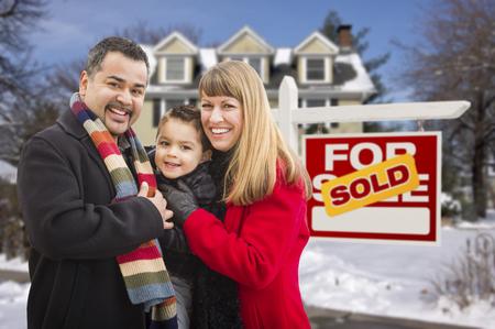 Warm gekleed jong gemengd ras Familie voor verkochte huis voor verkoop onroerend goed teken en huis met sneeuw op de grond.