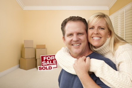 Happy Affectionate Couple in Room of New House With Only Boxes on the Floor. photo