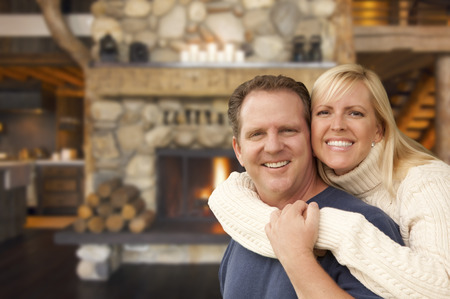 winter wedding: Happy Affectionate Couple at Rustic Fireplace in Log Cabin. Stock Photo
