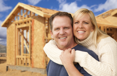 Happy Excited Couple in Front of Their New Home Construction Framing Site. Stock Photo