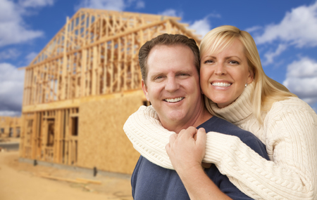 home front: Happy Excited Couple in Front of Their New Home Construction Framing Site. Stock Photo