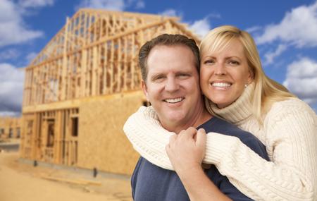 pareja en casa: Pareja emocionado feliz en frente de su casa nueva construcci�n encuadre sitio.