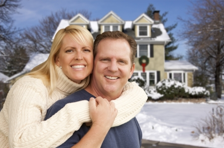 Happy Couple in Front of Beautiful House with Snow on the Ground. photo