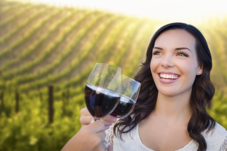 Pretty Mixed Race Young Adult Woman Enjoying A Glass of Wine in the Vineyard with Friends. Stock Photo