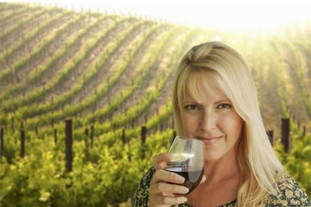 幸せな魅力的な女性は、ブドウ畑でワインのグラスを楽しみます。