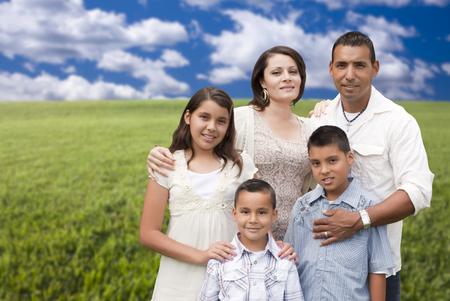 Gelukkige Spaanse Familie Portret staande in grasveld.