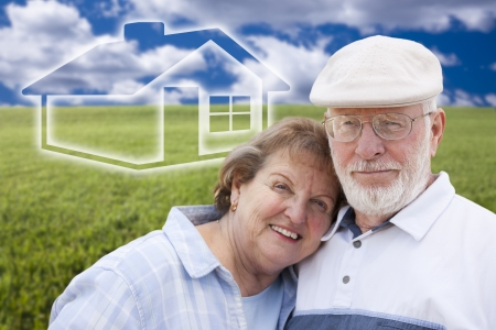 Loving Senior Couple Standing in Grass Field with Ghosted House on the Horizon. photo