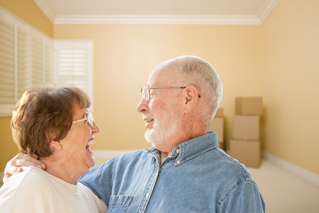 relocating: Happy Senior Couple In Room with Moving Boxes on the Floor.
