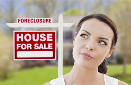 foreclosure: Thoughtful Pretty Mixed Race Woman In Front of Home and Foreclosure House For Sale Real Estate Sign Looking Up and to the Side.