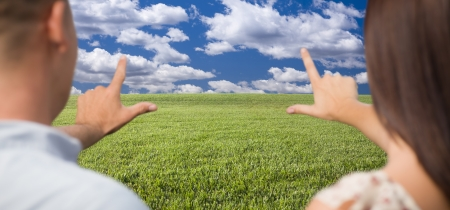 Couple Framing Hands Around Space in Grass Field and Sky on the Horizon. Imagens
