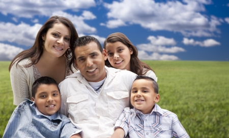 Happy Hispanic Family Portrait Sitting in Grass Field.