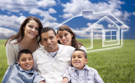 Happy Hispanic Family Portrait Sitting in Grass Field with Ghosted House Figure Behind. photo
