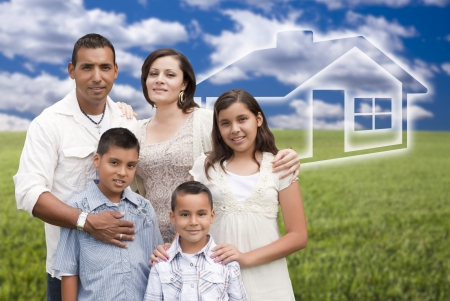 Happy Hispanic Family Standing in Grass Field with Ghosted House Behind. Stock Photo
