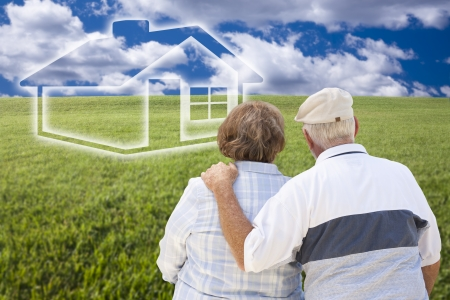 Loving Senior Couple Standing in Grass Field Looking Over at Ghosted House on the Horizon. photo