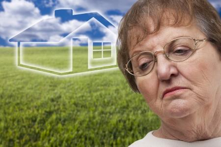 m�lancolie: Femme senior m�lancolie avec Green Grass Field et Ghosted Maison derri�re elle.