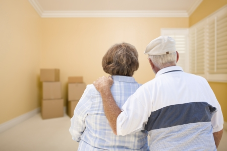 relocating: Hugging Senior Couple In Room Looking at Moving Boxes on the Floor.
