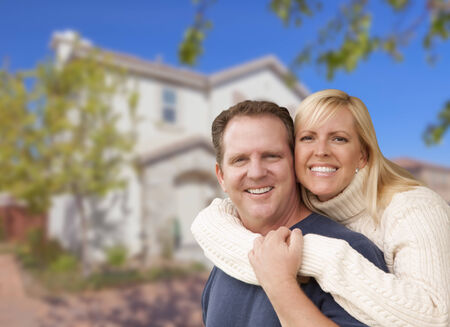 Happy Couple Hugging In Front of a Beautiful House. photo