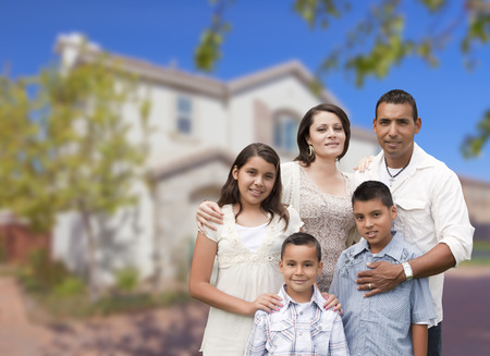front house: Happy Hispanic Family Portrait in Front of Beautiful House. Stock Photo