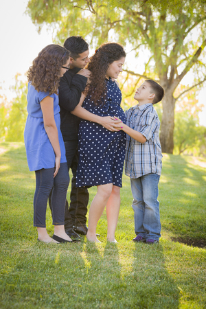 Happy Attractive Hispanic Family With Their Pregnant Mother Outdoors At the Park. photo