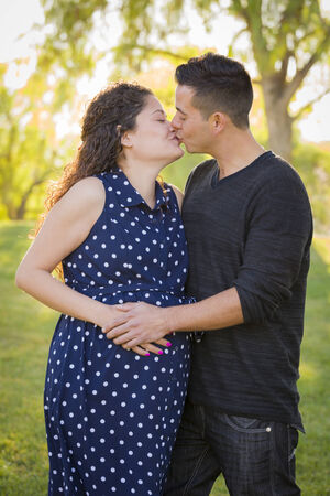 Hispanic Man Kisses His Pregnant Wife and Feels Their Baby Kick Outdoors At the Park. photo