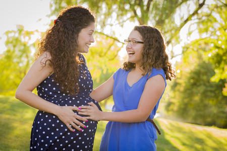 girl kick: Hispanic Daughter Feels Baby Kick in Pregnant Mother's Tummy Outdoors At the Park.