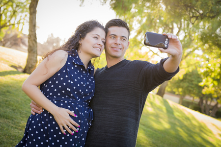 Pregnant Wife and Husband Taking Cell Phone Picture of Themselves Outdoors At The Park. photo
