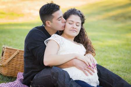 Peaceful Pregnant Hispanic Couple in The Park Outdoors. photo