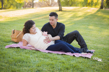 Contemplative Pregnant Hispanic Couple with Piggy Bank on Mothers Belly in the Park. photo