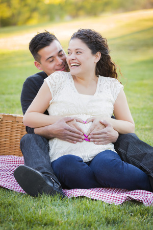 Pregnant Hispanic Couple Making Heart Shape with Hands on Belly in The Park Outdoors. photo