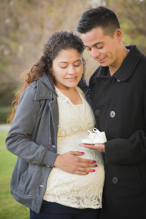Happy Hispanic Pregnant Couple Holding Baby Shoes Outside in the Park. photo