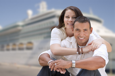 Young Happy Hispanic Couple Hugging On The Dock In Front of a Cruise Ship. Stock Photo