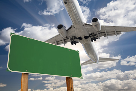 Blank Green Road Sign and Airplane Above with Dramatic Blue Sky and Clouds.