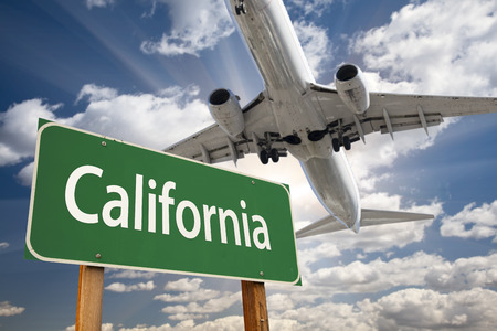 California Green Road Sign and Airplane Above with Dramatic Blue Sky and Clouds. photo