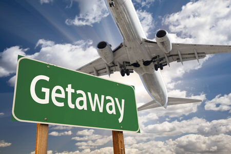 Getaway Green Road Sign and Airplane Above with Dramatic Blue Sky and Clouds. photo