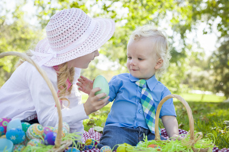 hunts: Cute Young Brother and Sister Enjoying Their Easter Eggs Outside in the Park Together.