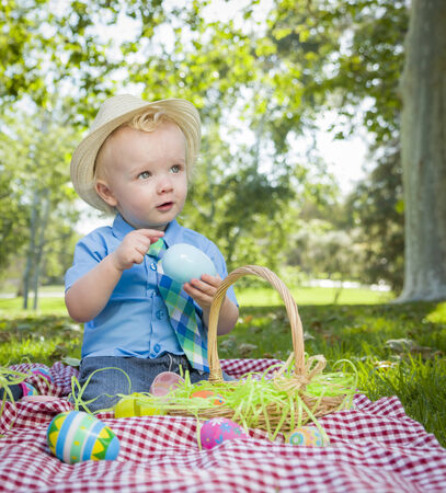 Cute Little Boy Wearing Hat Enjoying His Easter Eggs on Picnic Blanket Outside in the Park. photo
