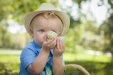 picnic blanket: Little Boy lindo que desgasta el sombrero Disfrutando de sus huevos de Pascua en Manta de picnic fuera en el parque.