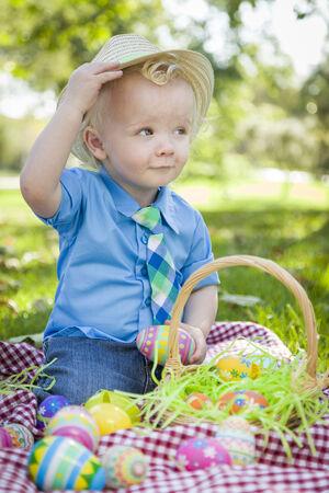 hunts: Cute Little Boy Outside On Picnic Blanket Holding Easter Eggs Tips His Hat.