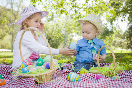 blue eyed: Cute Young Brother and Sister Enjoying Their Easter Eggs Outside in the Park Together.