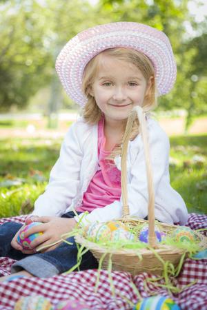 picnic blanket: Linda Chica joven en Manta de picnic que desgasta el sombrero goza de su huevos de Pascua fuera en el parque. Foto de archivo