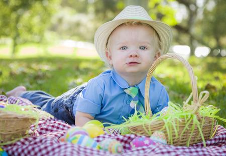 picnic blanket: Cute Little Boy que pone en Manta de picnic sonrisas con los huevos de Pascua Alrededor de �l. Foto de archivo