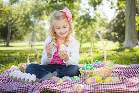 Cute Young Girl Happily Coloring Her Easter Eggs with Paint Brush in the Park.
