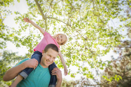 shoulder ride: Cute Young Girl Rides Piggyback On Her Dads Shoulders Outside at the Park.