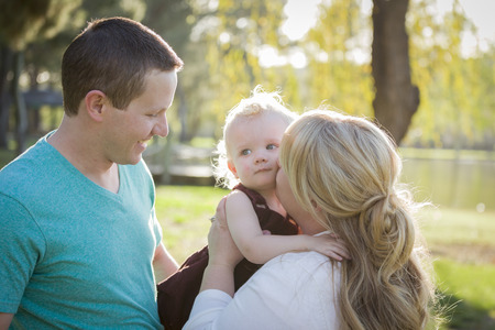 Cute Young Baby Boy Being Hugged By His Parents Outside at the Park. photo