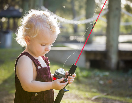 fishing pole: Cute Young Boy With Fishing Pole Outside at The Lake.