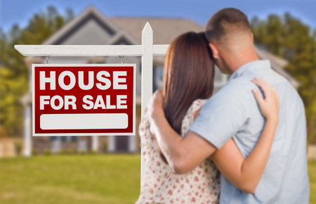 outside of house: For Sale Real Estate Sign and Affectionate Military Couple Looking at Nice New House