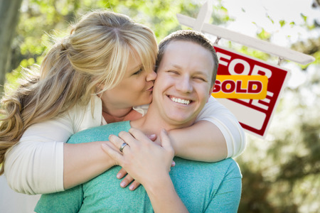 Happy Couple Hug In Front of Sold Real Estate Sign  photo
