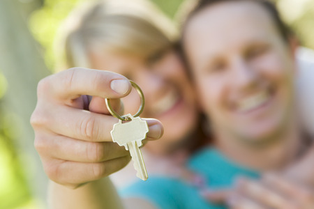 Happy Couple Holding Blank House Key Outside with Room For Your Own Text On The Key  photo