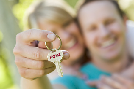 Happy Couple Holding House Key with Home Text On The Key  photo