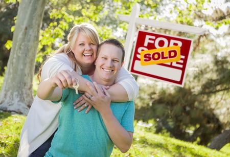Gelukkig Paar Holding huis sleutels voor Verkocht Real Estate Sign